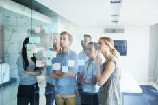 Shot of a group of colleagues brainstorming together with sticky notes in an office